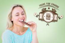 Pretty Blonde Enjoying And Eating Bar Of Chocolate  Against Green Vignette