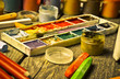 Tools for the artist. Inspiration to create. Objects for drawing. Paint, crayons, pencils on a wooden table.