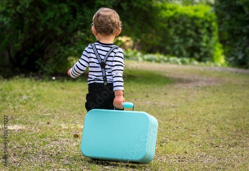 Valokuva  un petit garçon part en traînant une valise derrière lui