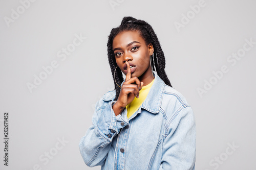 Photo  Beautiful Afro-American woman doing a silence gesture with her hand, isolated on