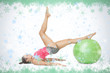 Attractive sporty brunette exercising with exercise ball against snow flake frame in green