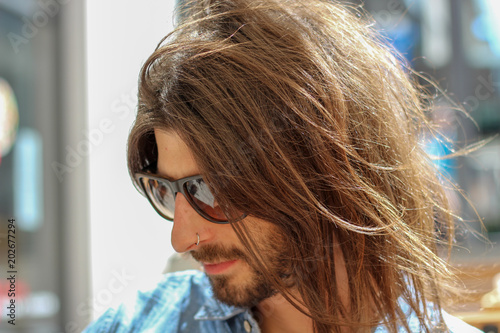 authentic handsome young man with long hair outdoors