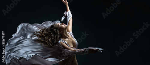 Beautiful brunette girl with curly hair in the darkness and light in sexy silver satin flying dress awesome poses in dance. Portrait art photo shooting in studio with female model