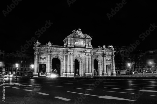 Night view of The Puerta de Alcala at night - a monument in the Independence Square in Madrid, Spain. Black and white