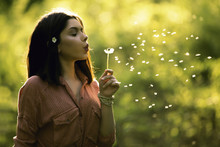 Young Teen Girl Blowing Dandelion
