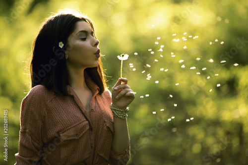 Young teen girl blowing dandelion Canvas Print