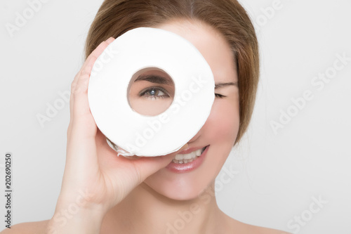 Fotografía  Beautiful woman looks through a roll of toilet paper