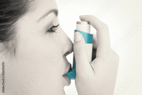 Woman with an asthma inhaler against white background Slika na platnu