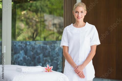 Photo  Smiling beauty therapist standing beside massage towel