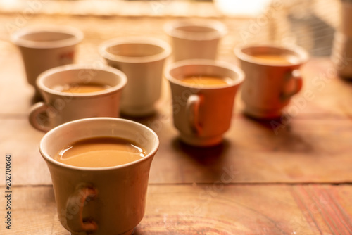 Fotografie, Tablou  Seven red cups of milk tea placing on wooden table