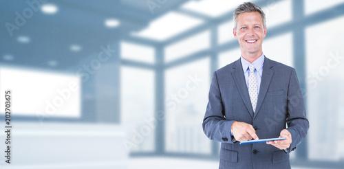 Photographie  Portrait of smiling businessman using digital tablet against modern room overloo