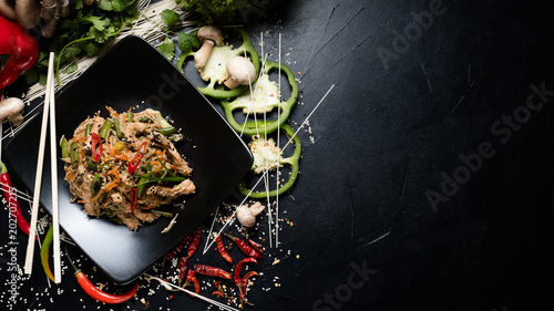 traditional oriental cuisine food preparing craft. rice noodle beef and vegetable on a plate. copyspace concept