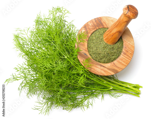 Fotografia dried dill weed in the wooden mortar, with fresh dill weed isolated on white, to