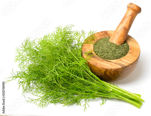 Valokuvatapetti dried dill weed in the wooden mortar, with fresh dill weed isolated on white