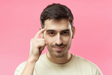 Closeup Portrait Of Young European Caucasian Man Pictured Isolated On Pink Background Pressing Finger To Temple As If Making Viewer Think More About Offer Or Analyze Information Better For Their Good