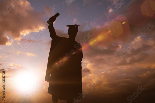 Fotografie, Obraz  Silhouette of graduate against sun shining