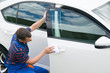 worker in a blue suit, wipes the car with a white rag