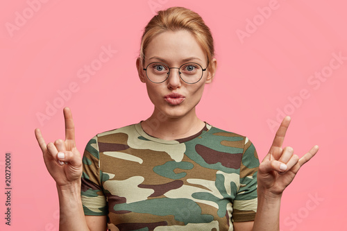 Valokuva  Cool beautiful blonde woman in eyewear shows peace sign, being satisfied with something, demonstrates her toughness, dressed in casual t shirt, isolated over pink background