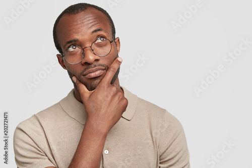 Fotografía  Portrait of thoughtful dark skinned enterpreneur being deep in thoughts, contemplates about successful business project, holds chin, looks pensively upwards, isolated over white studio background