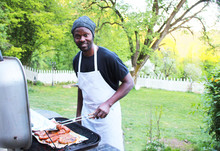 A Cheerful Man Grills Outdoors In The Park