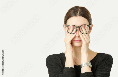 Fotografía  Portrait of young woman rubs her tired eyes