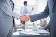 Business handshake against young business people in board room meeting