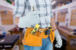Technician with tool belt around waist holding pliers against workshop