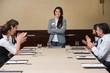 Businesswoman being applauded by peers