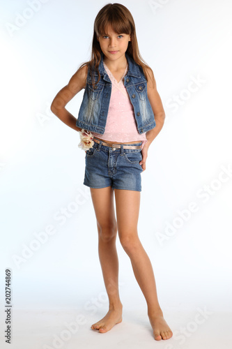 Láminas  Beautiful girl in a denim shorts is standing barefoot at full length