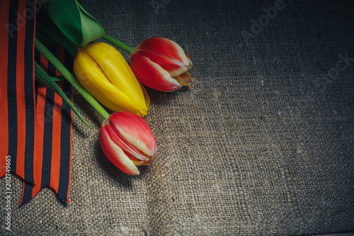 Fotografia  Military cap with order of Great Patriotic war and tulips flowers tied by Saint
