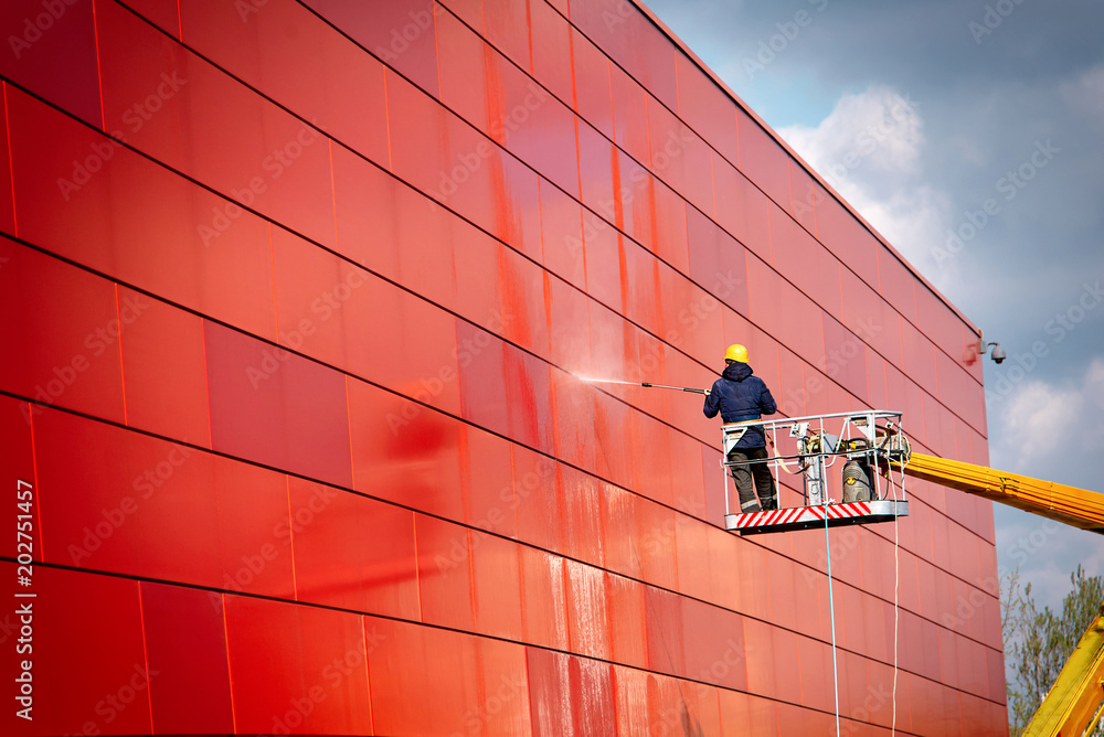 Fototapeta worker of Professional Facade Cleaning Services washing the red wall. Worker wearing safety harness washes wall facade at height on modern building in a crane.