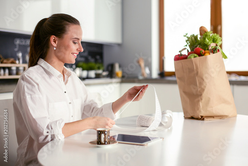 Fototapeta Young woman planning expenses and paying bills on her kitchen. obraz