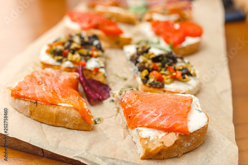 small sandwiches tapas with soft cheese and salmon on wood table