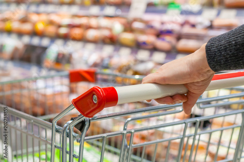 Obraz View of a female hand with pushcart in supermarket. The racks with the consumer goods in blur. Shallow depth of field - fototapety do salonu