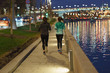 Sport activity on the Moscow embankment. Two women-runners in the night.