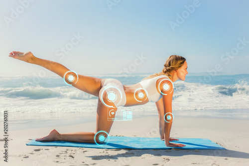 Fotografia  Gorgeous fit blonde in pilates pose on the beach against fitness interface