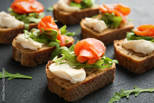 Photo sur Toile Entree Tasty sandwiches with fresh sliced salmon fillet on table