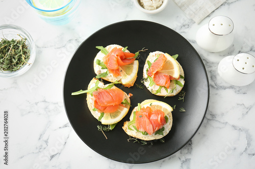 Photo sur Toile Entree Plate of tasty sandwiches with fresh sliced salmon fillet on table, top view