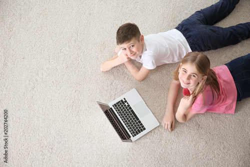 Fotografía  Teenage girl and her brother with laptop lying on cozy carpet at home