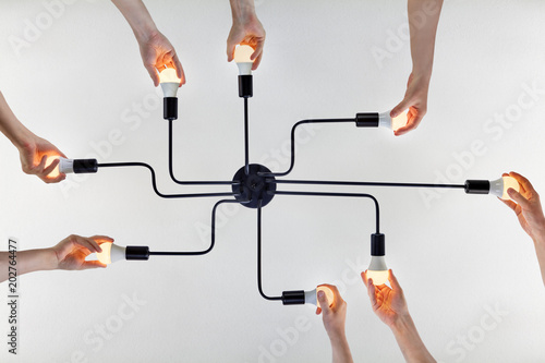 Fotomural Teamwork of collective when updating LED lamps in ceiling chandelier