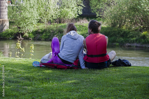 Fotografía  Young couple sitting on the river bank
