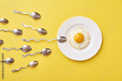 Valokuvatapetti Conception of fertilization. Fried egg in white plate, and spoon