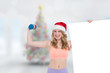 Festive fit blonde smiling at camera holding poster against blurry christmas tree in room