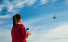 Female Flying A Drone At The Sky