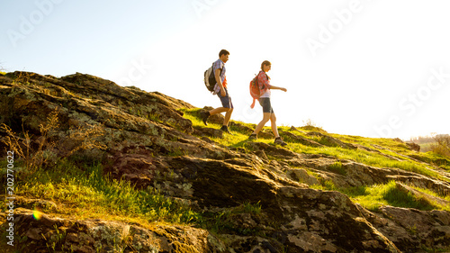 Fotografía  Young Happy Couple Hiking with Backpacks on the Beautiful Rocky Trail at Sunny Evening