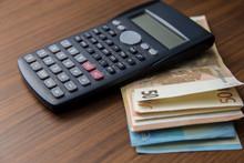 A Black Calculator With Euro Money.