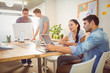 Creative business team gathered around laptops