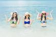 Three pretty beautiful asian women wearing colourful swimwear bikini with hat having fun and relax sunbathing on the beach in the summer