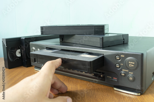 Valokuva  insert a videotape into a tape recorder