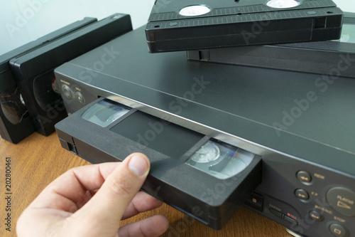 Fotografering insert a videotape into a tape recorder